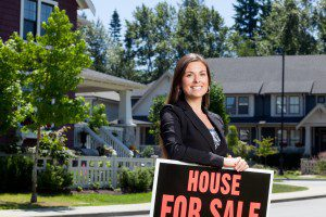 Professionally dressed real estate woman outside in a neighborhood leaning on a for sale sign.