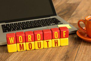 Word of Mouth written on a wooden cube in a office desk