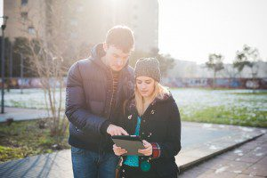 Knee figure of a couple of young beautiful caucasian woman and man strolling outdoor in the city back light, holding a tablet, looking downward and tapping the screen - love, technology, communication concept
